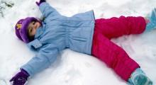 nina haciendo un angel de nieve