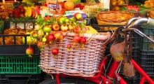 una bicicleta repleta de verduras al lado de una fruteria