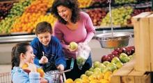 una madre con sus dos hijos al lado de las frutas de un supermercado